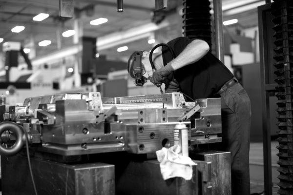 man welding a large machine part